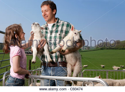 Shepherd and daughter holding lambs in pasture - Stock Photo