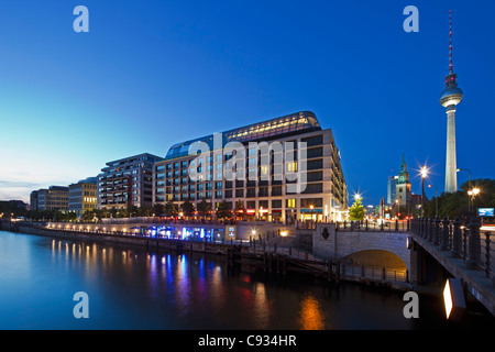 Twilight view of the Radisson Blu Hotel with the Berlin Fernsehturm Tower in the background, Mitte, Berlin, Germany. - Stock Photo