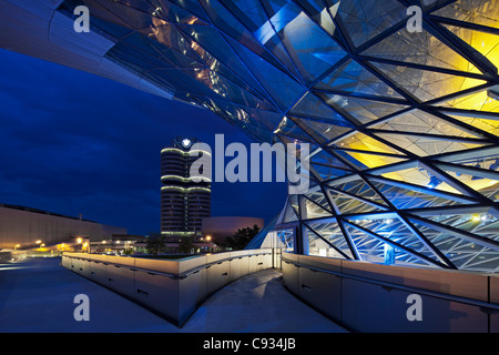 Twilight view of the pedestrian bridge link to the BMW Headquarters Office building and Museum, Munich, Bavaria, - Stock Photo