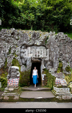 Bali, Ubud. A young woman emerges from exploring one of the shrines at the Goa Gajah Elephant Caves near Ubud. MR - Stock Photo