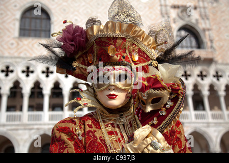 Venice, Veneto, Italy; A masked character in front of the 'Palazzo dei Dogi' during Carnival - Stock Photo