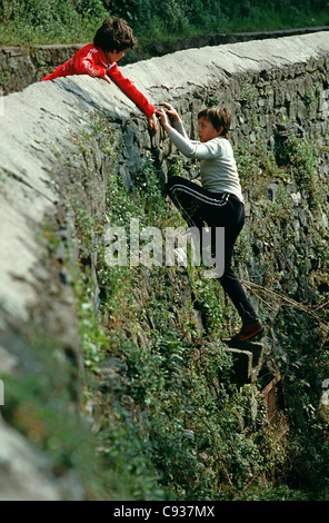 Two boys climbing stone wall in France - Stock Photo