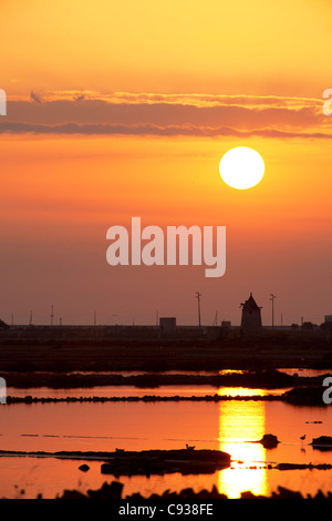 Sicily, Italy, Western Europe; A mill in the historic saltpans between Trapani and Marsala at sunset - Stock Photo