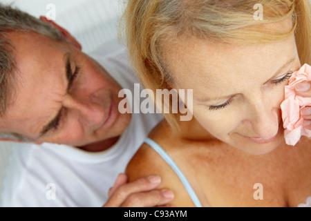 Man comforting crying wife - Stock Photo