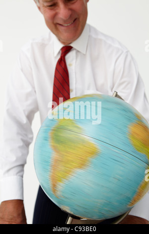Senior businessman spinning globe - Stock Photo