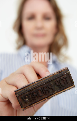 Businesswoman with rubber stamp - Stock Photo