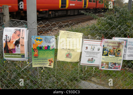 adverts for forthcoming events and courses fixed to a fence adjacent to a railway track in mortlake, southwest london, - Stock Photo