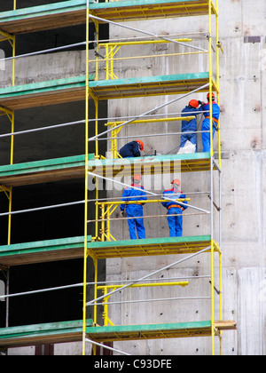 Men working on a scaffold on a new concrete building, wearing brightly colored protective clothing - Stock Photo