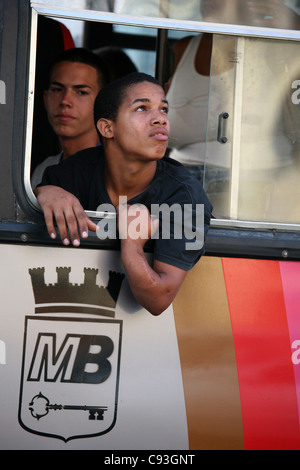 Cuban boy looks out from the public bus in Havana, Cuba. - Stock Photo