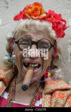 Eccentric old Cuban woman smoking cigar in the historical centre of Havana, Cuba. - Stock Photo