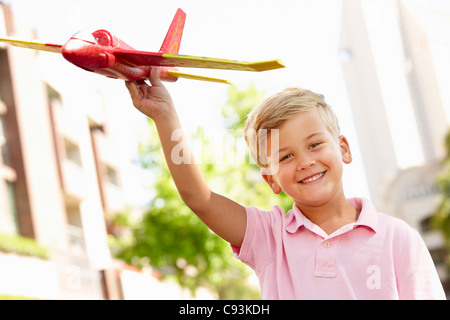 Young boy outside with toy aeroplane - Stock Photo