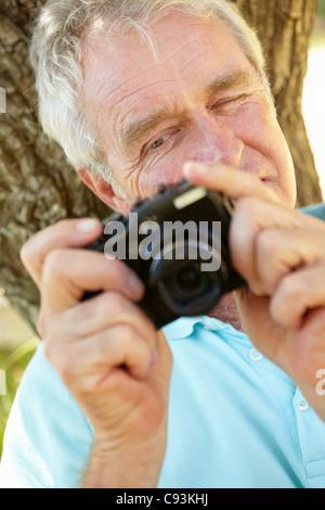 Senior man with camera - Stock Photo