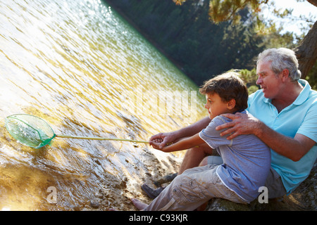 Grandfather and grandson with fishing net - Stock Photo