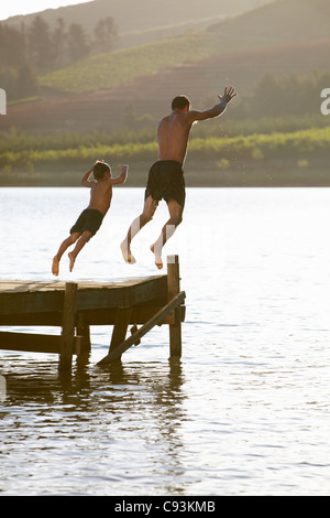 Father and son jumping off jetty - Stock Photo