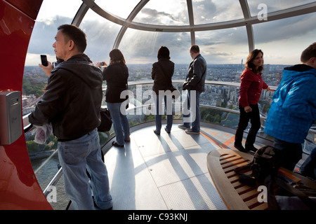 Tourists in the London eye cabin observing city from birds view on June 10, 2011, Londun, UK. - Stock Photo