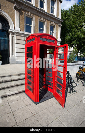 Old red phone booth with open door in London - Stock Photo