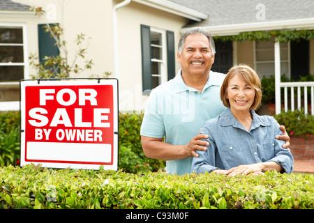 Senior Hispanic couple selling house - Stock Photo