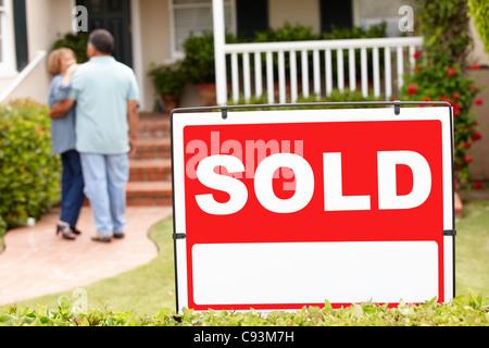 Senior Hispanic couple moving into new home - Stock Photo