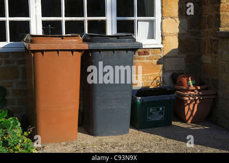 Wheelie bins, brown for garden waste and black for household rubbish, and a box for recyclables. - Stock Photo