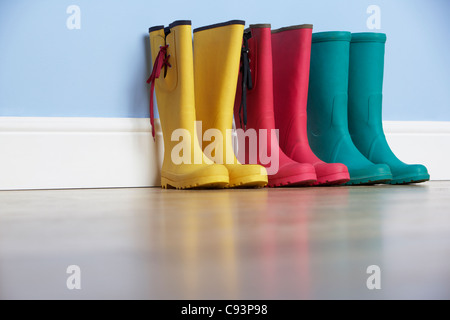 Wellingtons lines up against wall - Stock Photo