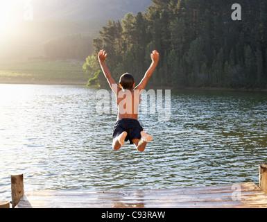 Young boy jumping into lake - Stock Photo