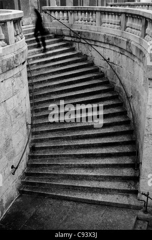 Person climbing curvy stairs - Stock Photo