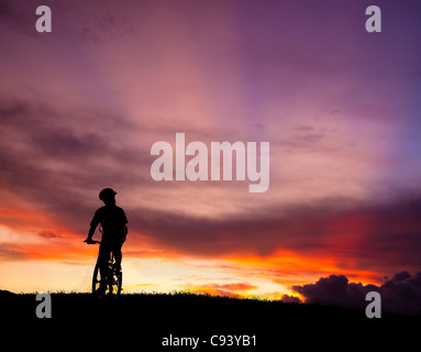The silhouette of mountain bicycle rider on the hill with beautiful sunrise background - Stock Photo