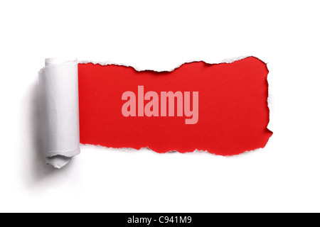 Tearing a paper frame hole with red background - Stock Photo
