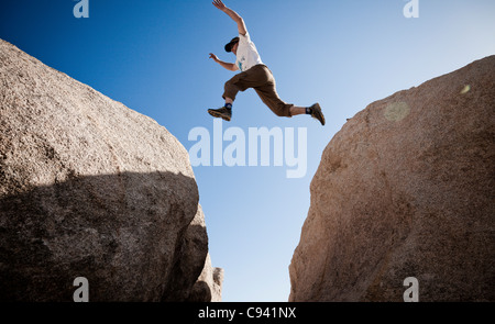 Man Leaping between Two Boulders - Stock Photo