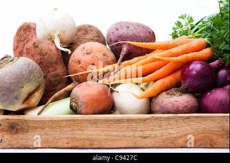 Box of mixed vegetables: turnips, carrots, swede, potatoes, beetroots and red onions - Stock Photo