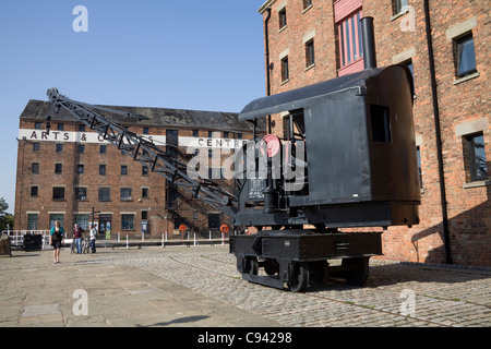 Gloucester England Crane on quayside of renovated Dock Basin with Arts and Crafts Antiques Centre behind - Stock Photo