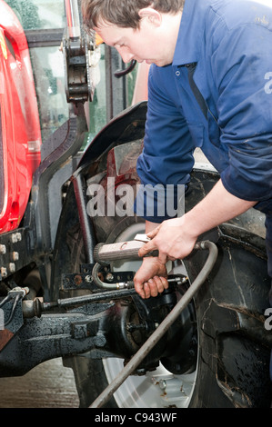 Mechanic checking the tyre pressure in tractor tyres - Stock Photo