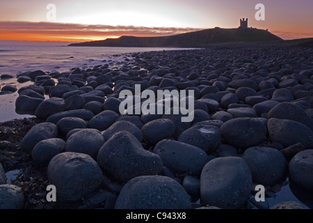 Sunrise at Dunstanburgh Castle, Northumberland, with rocky outcrops below - Stock Photo