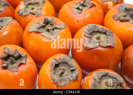Red juicy persimmons isolated on white background - Stock Photo