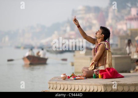 Sadhu praying on the ghats lining the River Ganges, with a rowboat in the background, Varanasi, Uttar Pradesh, India - Stock Photo