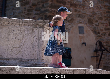 Two very young Italian children stand by a fountain with the girl holding her stuffed animal posing to have their - Stock Photo
