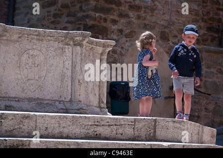 Two very young Italian children stand on the top marble steps of a fountain in with the girl holding her stuffed - Stock Photo