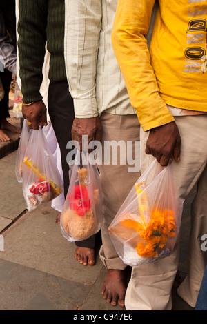India, Assam, Guwahati, Kamakhya temple, hands of pilgrims holding offerings waiting to enter the Shikara - Stock Photo