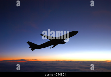 Passenger plane during flight and blue sky after sunset. - Stock Photo