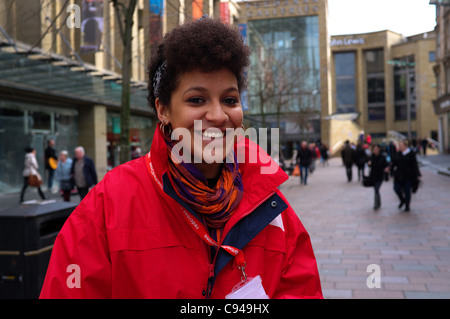 Young woman acting as a Street canvasser for the British Red Cross Charity in Sauchiehall Street, Glasgow - Stock Photo