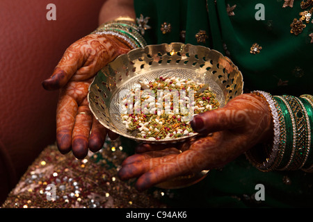 India, Assam, Guwahati, traditional mehndi henna decorative patterns on hands of bride holding bowl of sof - Stock Photo