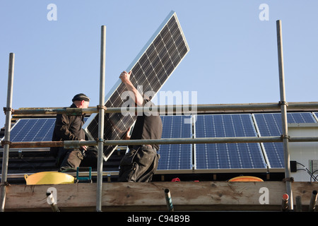 Workmen fitting new solar panels to a residential house roof for the Feed-in Tariff scheme. Wales, UK, Britain