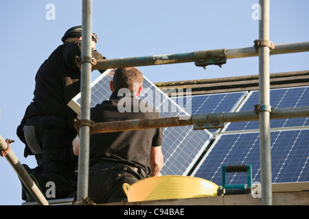 UK, Britain, Europe. Workmen installing new solar panels to a house roof for the Feed-in Tariff scheme - Stock Photo