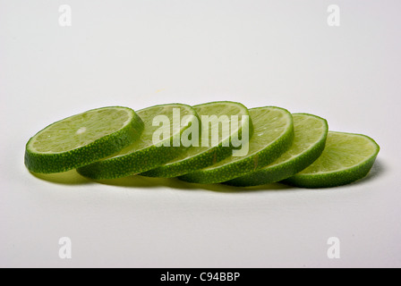 Lime slices lay on a plain background. - Stock Photo