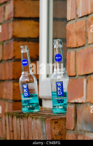 Two bottles of WKD Blue on a window sill after a night out. - Stock Photo