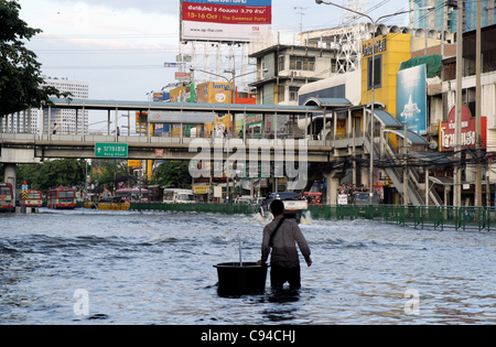 A man wading through floodwaters on street on November 12, 2011 in ladprao district, Bangkok, Thailand. Over seven - Stock Photo