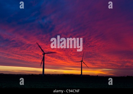 2 wind turbines, a hedge and a field, silhouetted against a stormy/glorious sunrise - Stock Photo