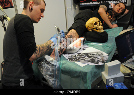 12.11.2011 Warsaw, Poland. Man gets a new tattoo on his leg during the first day of tattoo, body painting and pierceing - Stock Photo