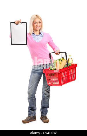 Full length portrait of a female holding a shopping basket and showing a clipboard - Stock Photo