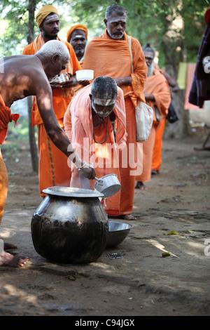 Men sadhu receiving free food Arunachala South India - Stock Photo